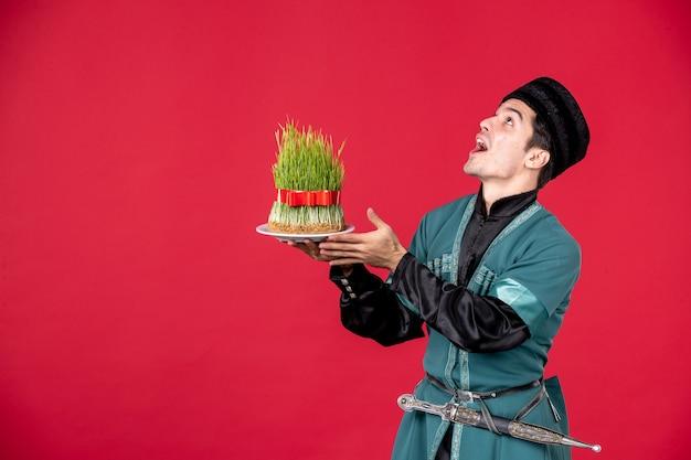 Ritratto di uomo azero in costume tradizionale azienda semeni studio shot concetto rosso novruz ballerini primavera