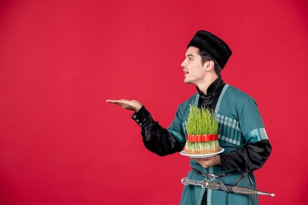 Ritratto di uomo azero in costume tradizionale azienda semeni studio shot concetto rosso novruz performer spring