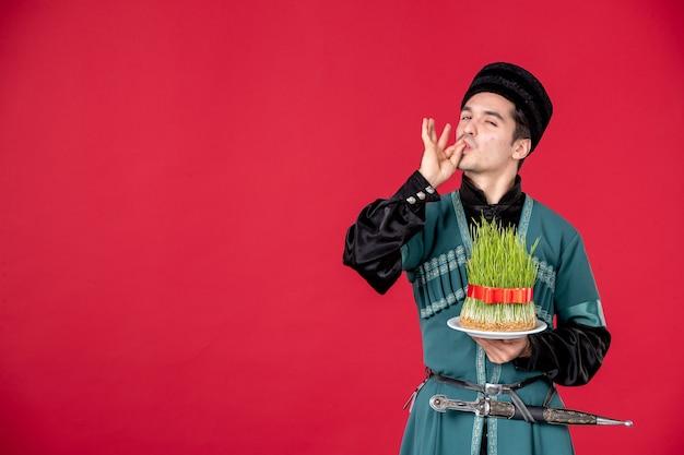 Ritratto di uomo azero in costume tradizionale che tiene semeni studio shot red concept performer spring