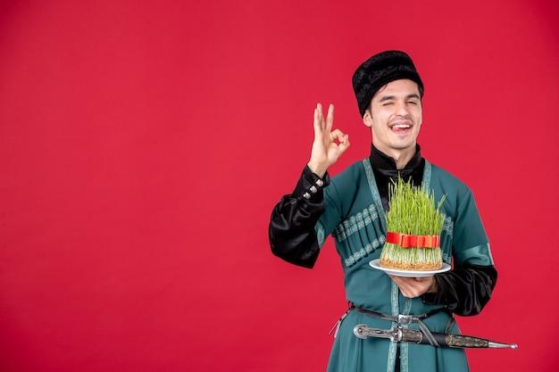 Ritratto di uomo azero in costume tradizionale azienda semeni studio shot concetto rosso esecutori primavera novruz