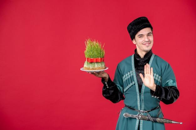 Ritratto di uomo azero in costume tradizionale azienda semeni studio shot ballerino rosso novruz primavera
