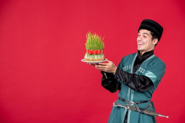 Ritratto di uomo azero in costume tradizionale azienda semeni studio shot ballerino rosso primavera novruz