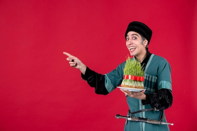 Ritratto di uomo azero in costume tradizionale con semeni su colori rossi ballerino vacanza novruz primavera etnica