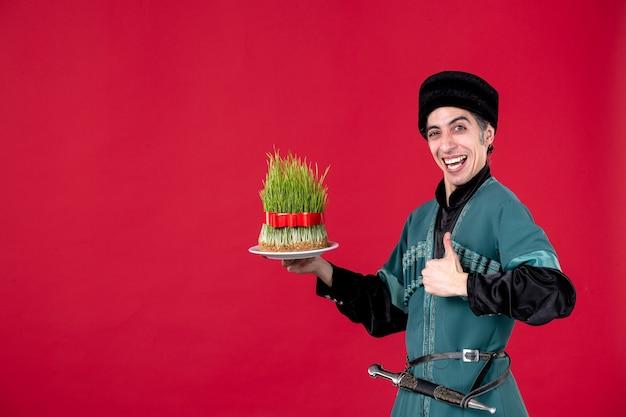 Ritratto dell'uomo azero in costume tradizionale con semeni sulla primavera etnica novruz di festa del ballerino rosso
