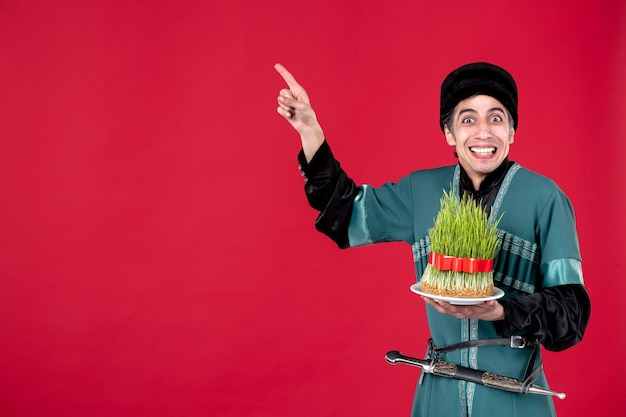 Portrait of azeri man in traditional costume with semeni on red ethnic dancer holiday novruz