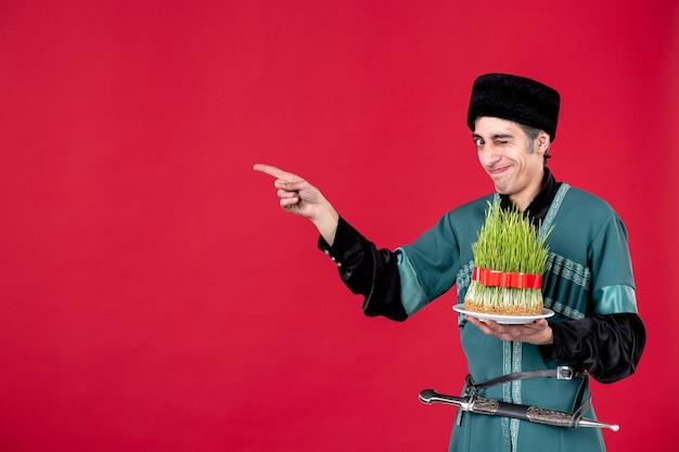 Ritratto di uomo azero in costume tradizionale con semeni sulla primavera rossa delle vacanze del ballerino di novruz