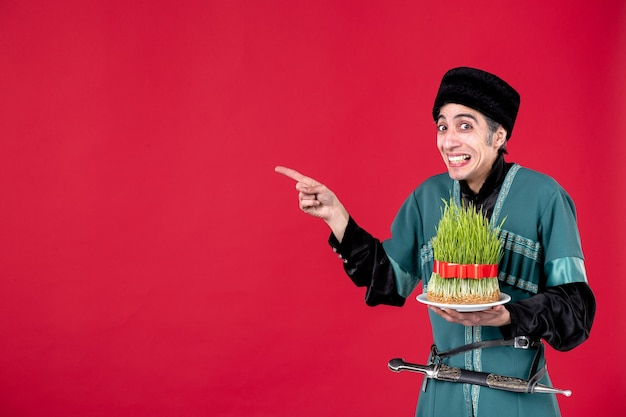 Ritratto di uomo azero in costume tradizionale con semeni su ballerino di festa etnica novruz rosso