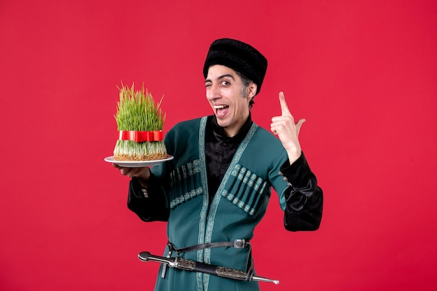 Portrait of azeri man in traditional costume with semeni on red