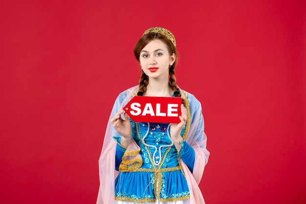 Portrait of azeri woman in traditional dress holding sale nameplate on red