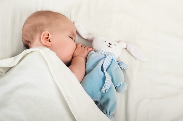 Portrait of baby 6 months sleeping with toy hare. toddler, teething, baby sleep concept.
