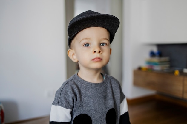 Portrait of a baby boy. a cute male toddler in a sweatshirt and a hat is watching from the side indoor space of the house. the boy has a vague facial expression. love, family, home