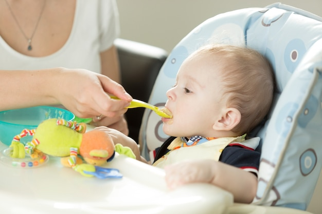 Portrait of baby boy eating in highchair at kitchen