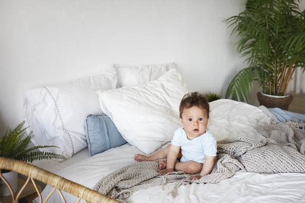 A portrait baby boy sitting upright on the bed