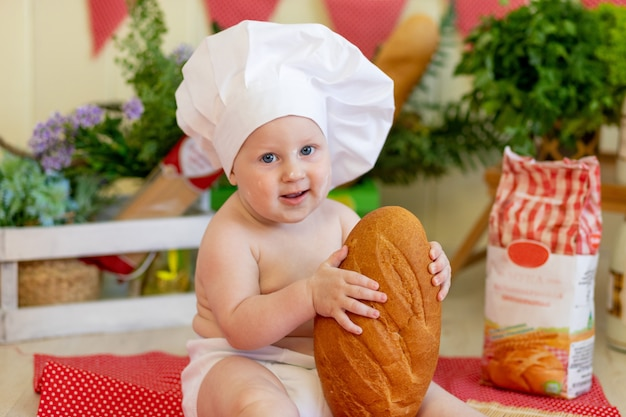 Portrait of a baby in a cook's hat with bread in his hands in a beautiful photo zone with flour and vegetables, a cook's child, a child eating bread, preparing food