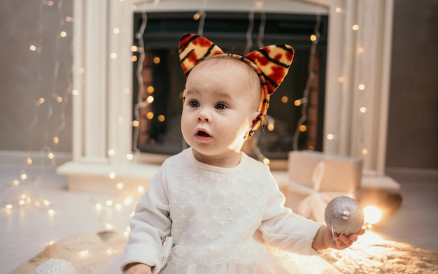 Portrait of a baby girl in a fluffy dress and a headband with tiger ears sitting near the fireplace in the room and playing with christmas balls
