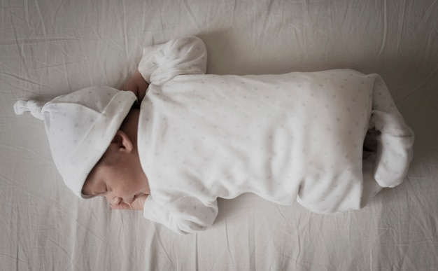 Portrait of baby sleeping on white sheets