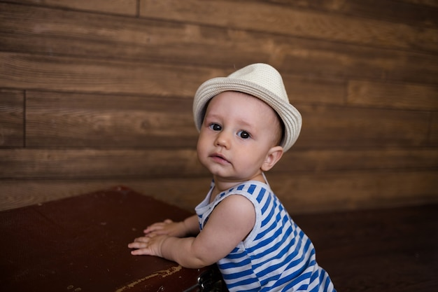 Portrait of a baby in a straw hat and a retro suitcase on a wooden background with space for text