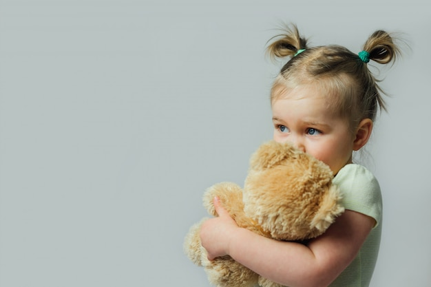Portrait of baby toddler holding soft toy looking away