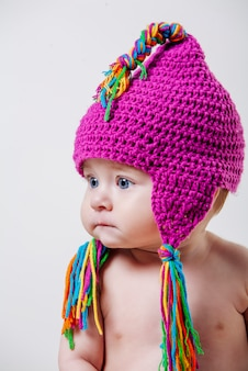 Portrait of a baby with pink wool hat and colored fringes
