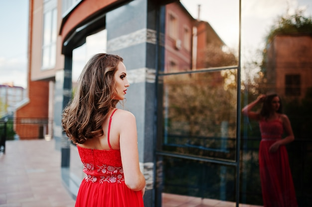 Portrait back of fashionable girl at red evening dress posed background mirror window of modern building