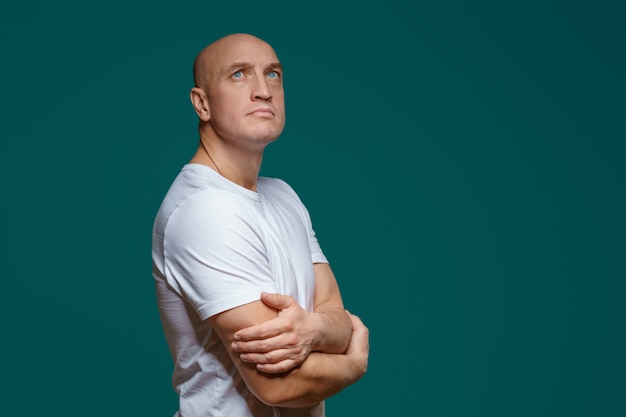Portrait of a bald adult man with a sad expression in a white t shirt on a blue surface