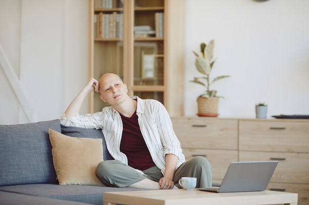 Portrait of bald adult woman looking away pensively while sitting on couch in modern home interior, alopecia and cancer awareness, copy space