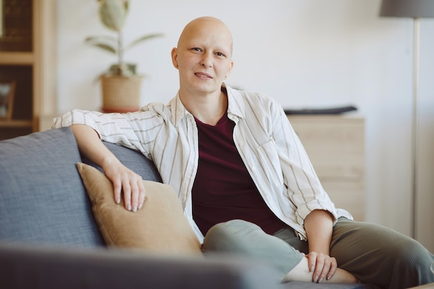 Portrait of bald adult woman looking at camera while sitting on couch in modern home interior, alopecia and cancer awareness, copy space