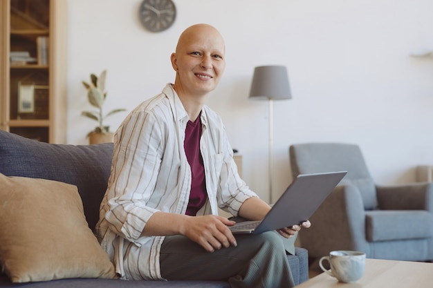 Portrait of bald adult woman smiling at camera while using laptop sitting on couch in modern home interior, alopecia and cancer awareness, copy space