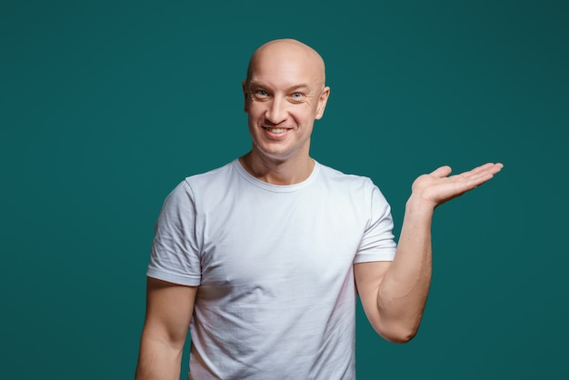 Portrait of a bald cheerful man holding his hand to the side shows a gesture to the side