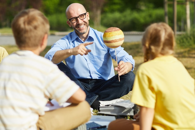 Portrait of bald male teacher pointing at planet model and smiling while talking to group of children during outdoor class in sunlight, copy space