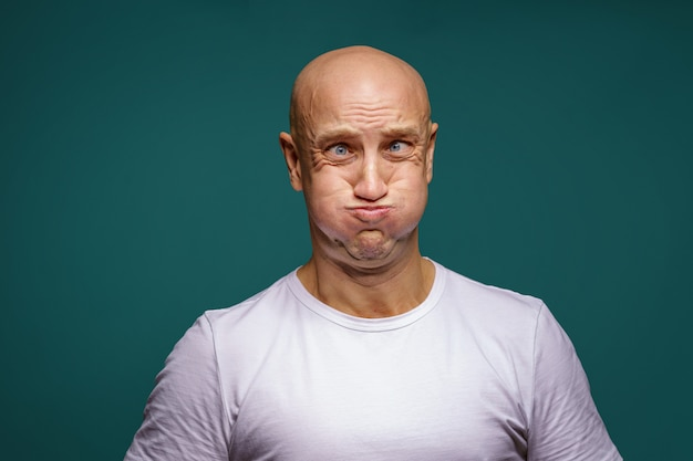 Portrait of a bald man puffed out his cheeks