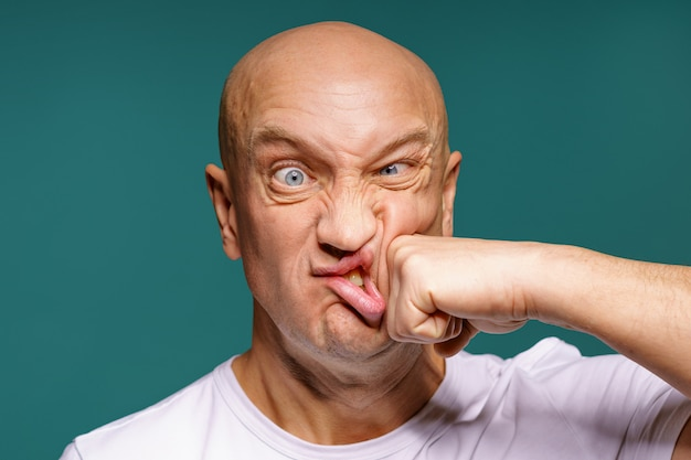Portrait of a bald man punches himself on the cheek, facial expressions