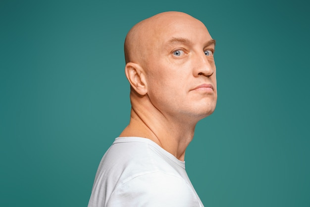 Portrait of a bald man in a white t-shirt on the , facial expression
