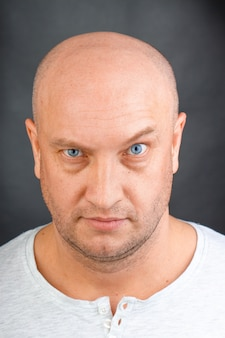 Portrait of a bald man with blue eyes close up