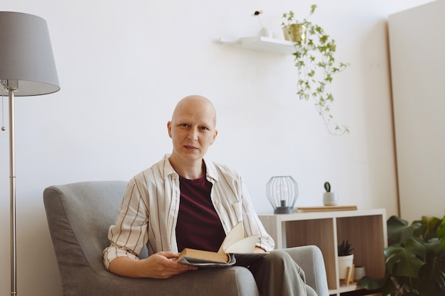 Portrait of bald mature woman looking at camera while reading book sitting in comfortable armchair at home, alopecia and cancer awareness, copy space