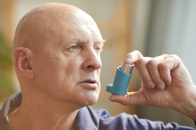 Portrait of bald senior man using inhaler for asthma or breathing problems in home interior