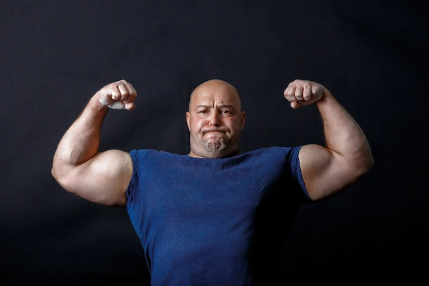 A portrait of bald strongman in dark t-shirt