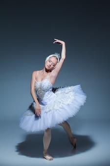 Ritratto della ballerina nel ruolo di un cigno bianco su sfondo blu