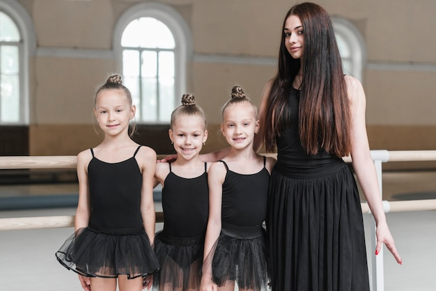 Portrait of ballerina teacher with her three student in dance studio