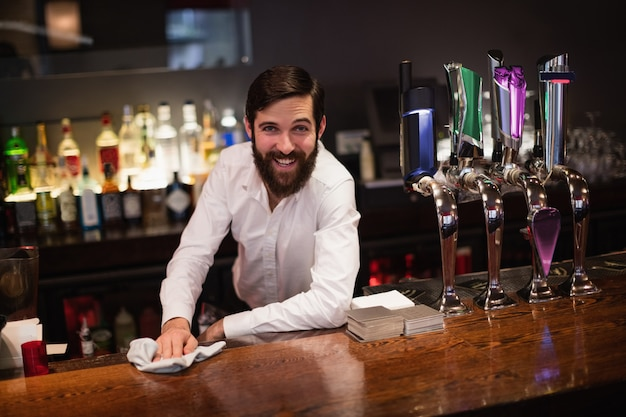 Portrait of bartender cleaning bar counter
