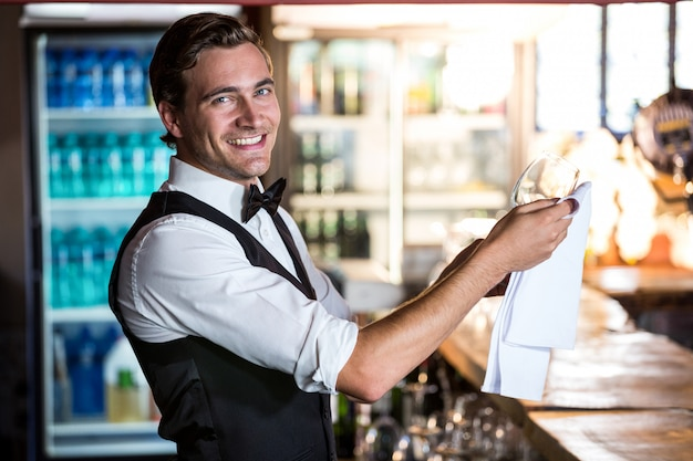 Portrait of bartender cleaning wineglass