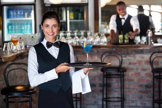 Portrait of bartender holding serving tray with glass of cocktail