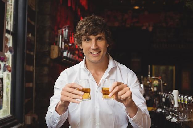 Portrait of bartender holding whisky shot glasses at bar counter