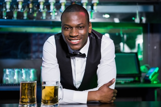 Portrait of bartender leaning and smiling on bar counter with two glasses of beer in front of him