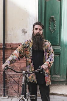 Portrait of a beard man with his bicycle looking at camera