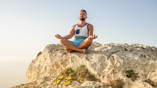 Portrait of bearded adult man making lotus pose
