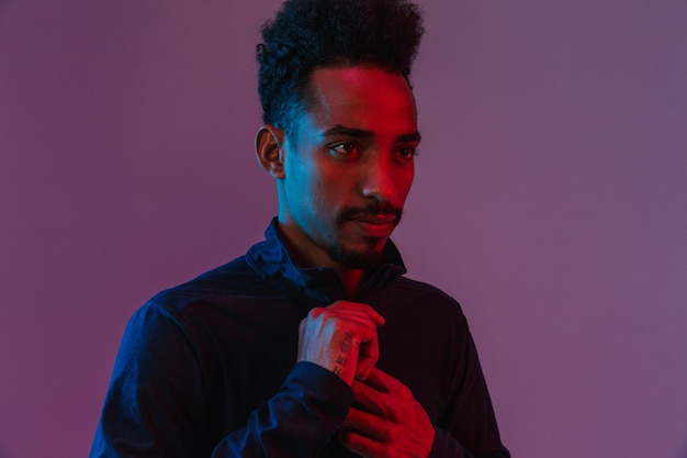 Portrait of bearded african american man in sportswear posingisolated over violet wall