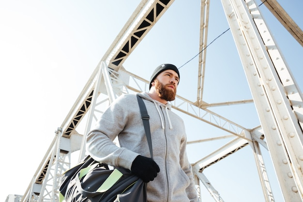 Portrait of a bearded athlete with sports bag walking along urban bridge