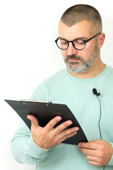 Portrait of bearded businessman coach wearing glasses with microphone and clipboard. mentor speaker holding online lesson