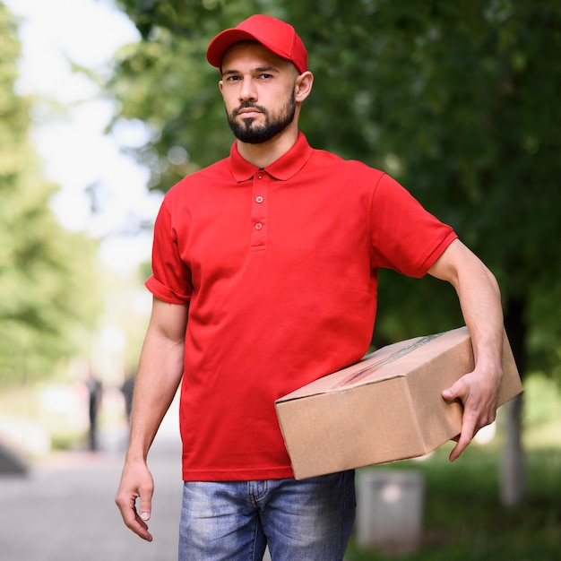 Portrait of bearded delivery man holding box